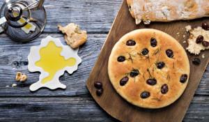 Ein Holzbrett mit einer runden Focaccia und einem Oliven-Parmesan-Ciabatta. Daneben eine Schale mit frischem Olivenöl.