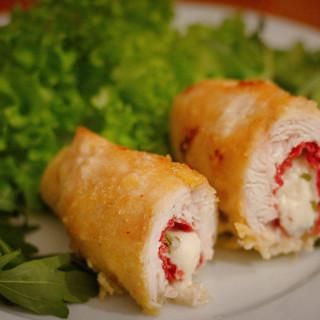 Auf einem Rucolabett liegt eine aufgeschnittene Hühnerroulade, die mit Bresaola, Mozzarella und Rosmarin gefüllt ist.