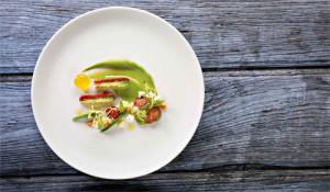 Das Bild zeigt einen weißen Teller auf grauem Holzuntergrund. Darauf angerichtet Olivenöl in Gelee, Guacamole, Tomaten, Feta.