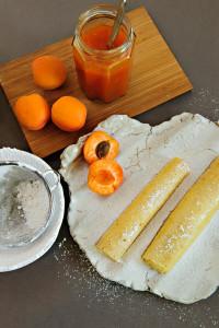 Zwei Palatschinken, daneben ein Glas Marillenmarmelade und frische Aprikosen