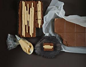 Eine Form mit Bernie Rieders Schokoladentarte mit Vanillekipferlcreme. Daneben eine angebrochene Schokolade und eine Spritztülle mit der Creme.