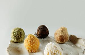 Fünf verschiedene Topfenknödel auf einem Teller. Darunter Varianten mit Petersilie oder Kokos.