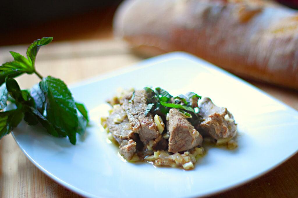 Ein weißer Teller mit kleinen Lammfleischstückchen, gehackten Mandeln und Zwiebeln, garniert mit Koriander und Minze.