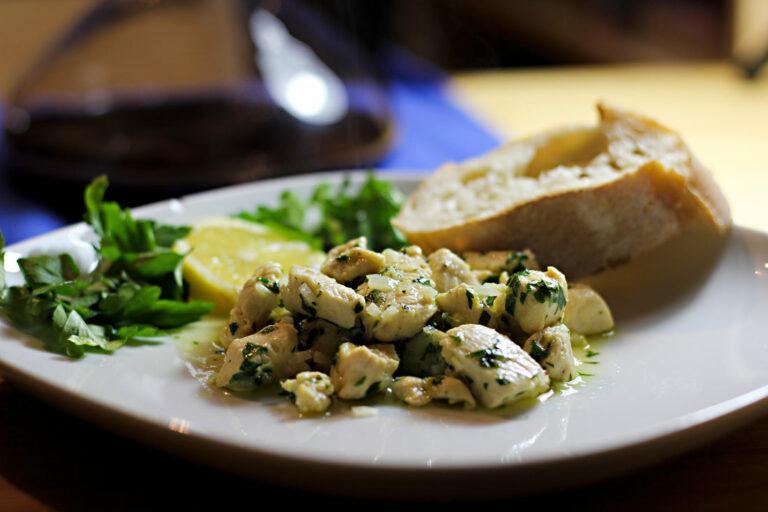 Ein Teller mit gewürfeltem, gebratenen Hühnerfleisch in einer Zitronensauce mit Knoblauch und Petersilie. Im Hintergrund liegt eine Scheibe Ciabatta und eine Deko aus Zitrone und Petersilie.