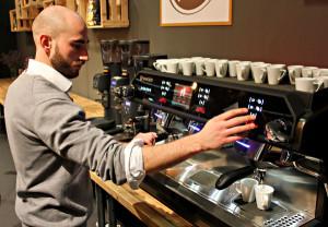 Ein Barista steht vor einer Espressomaschine, wie man sie in Bars findet, und brüht frischen Espresso.