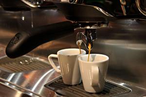 Das Bild zeigt zwei Espressotassen unter einem Siebträger, aus dem frischer Espresso fließt.
