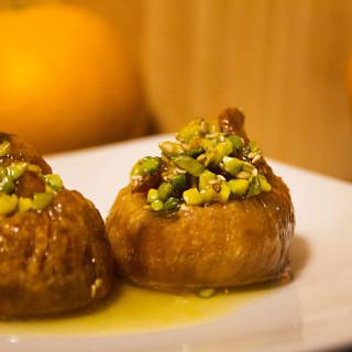 Zwei Feigen im Orangen-Honig-Sud auf einem Teller. Sie sind mit Pistazien gefüllt.