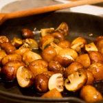 In einer gusseisernen Pfanne werden Champignons angebraten.