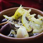 Eine braune Tonschüssel mit marinierten Oliven, Sardellen, Zitronenscheiben und Knoblauch