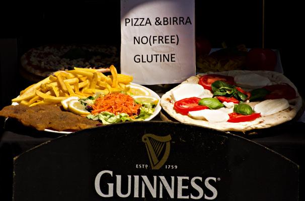 Touristenfraß: Ein Foto eines Tellers mit Pommes und Schnitzel, daneben eine Pizza. Davor ein Guiness-Schild