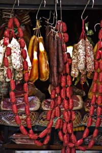 Ein Bild der Auslage eines Wurstwarengeschäfts mit jede Menge Salami, Würsten und Schinken.