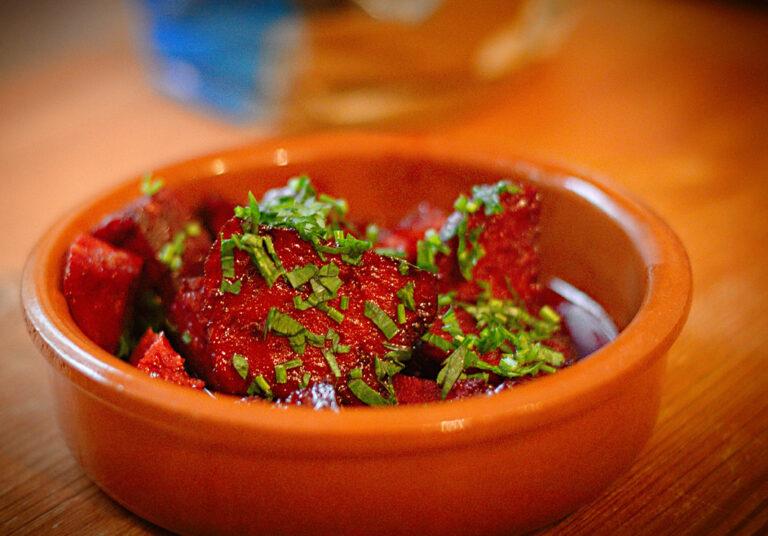 Eine kleine Tonschale mit Chorizo-Stücken in Rotwein. Garniert mit Petersilie.