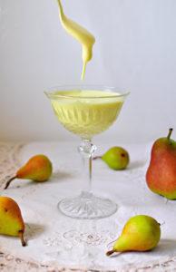 Ein Dessertglas mit Zabaione, von einem Löffel tropft Zabaione ins Glas. Um das Glas, das auf einer Decke steht, sind kleine Birnen verteilt.