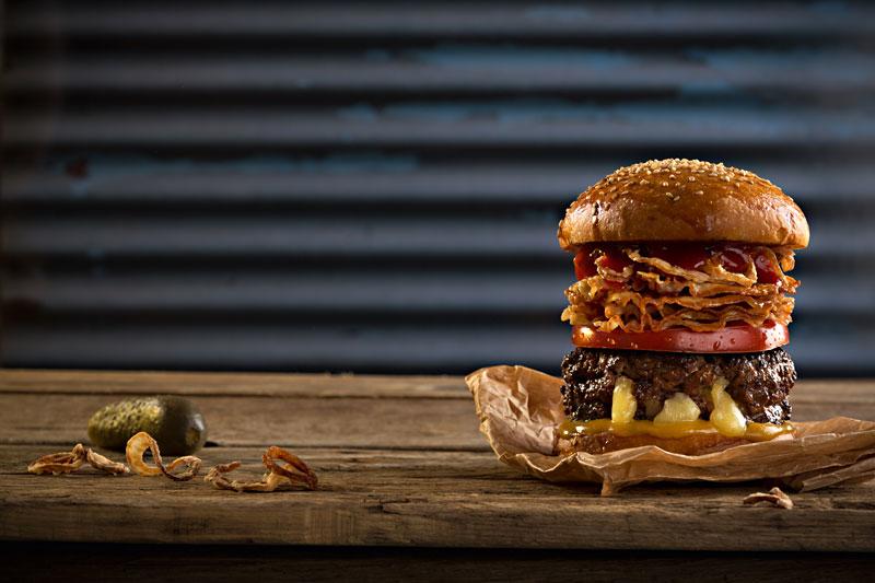 Auf einem Holzbrett liegt ein Burger, für den man mindestens den Unterkiefer ausrenken muss. Der sehr hohe Bad-Ass-Burger schichtet auf der Bulette eine Scheibe Tomate und ganz viel krosse Pancetta.