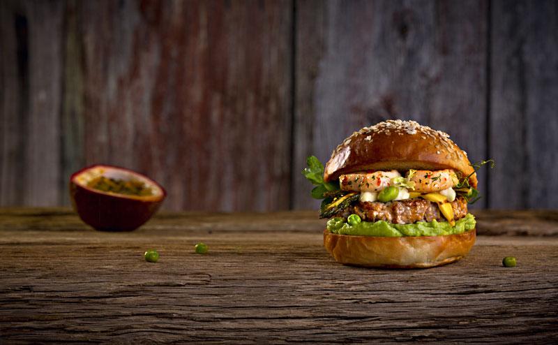 Ein wirklich schöner Burger auf hölzernem Boden: Der schöne Jacques schichtet Erbsencreme, Kalbsbulette, Mango und Jakobsmuscheln.