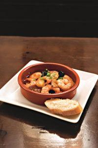 Auf einem weißen Teller steht eine Tapas-Schale mit gebratenen Garnelen in Knoblauchsauce. Daneben eine Scheibe Baguette.