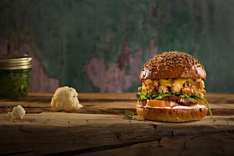 Auf einem massiven Holztisch liegt der vegetarische Burger Vegetanium. Auf dem Bun schichtet sich Süßkartoffel, Apfel, Zuckerschoten und Blumenkohl. Darauf die Oberseite des Buns.