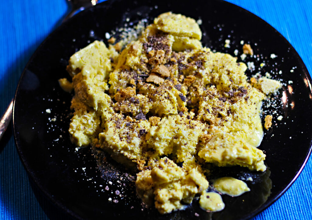 Ein Teller mit Dänischem Butterkeks-Schmarrn, bestreut mit Mandelkrokant, geraspelter Schokolade und Amarettibröseln