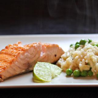 Ein Teller mit noch dampfenden Erbsenrisotto und einem Lachsfilet, garniert mit einer Limettenspalte