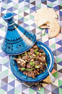 Eine offene blaue Tajine. Sie ist mit Lammfleisch mit Pflaumen und Mandeln gefüllt.