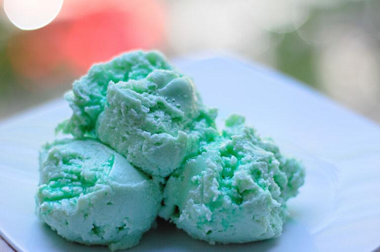 Auf einem Dessertteller sind drei Kugeln grünes Waldmeistereis angerichtet.