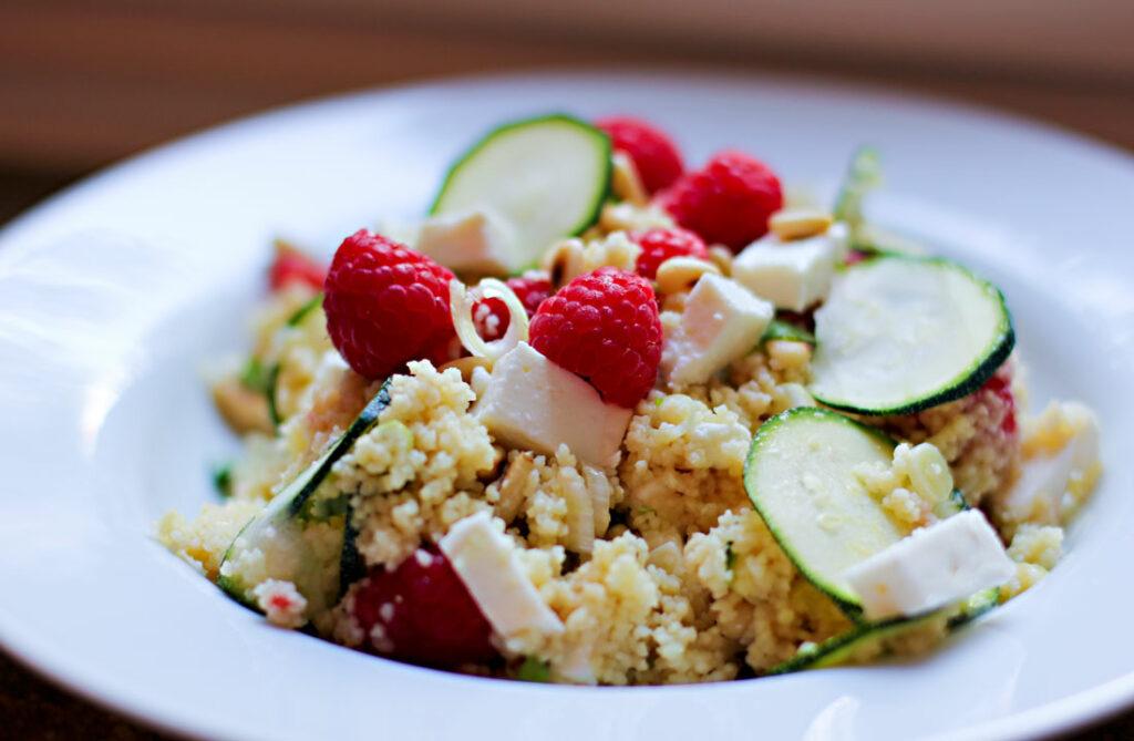 Ein weißer Teller mit einem Couscous-Salat, der mit Zucchinischeiben, Frühlingszwiebeln und vor allem mit Himbeeren und Feta zubereitet ist.