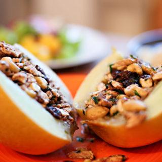 Ein Teller mit einer halbierten Melone, die mit einer Mischung aus Hähnchenfleisch, Cashewkernen, Mandeln und Cranberries gefüllt ist.