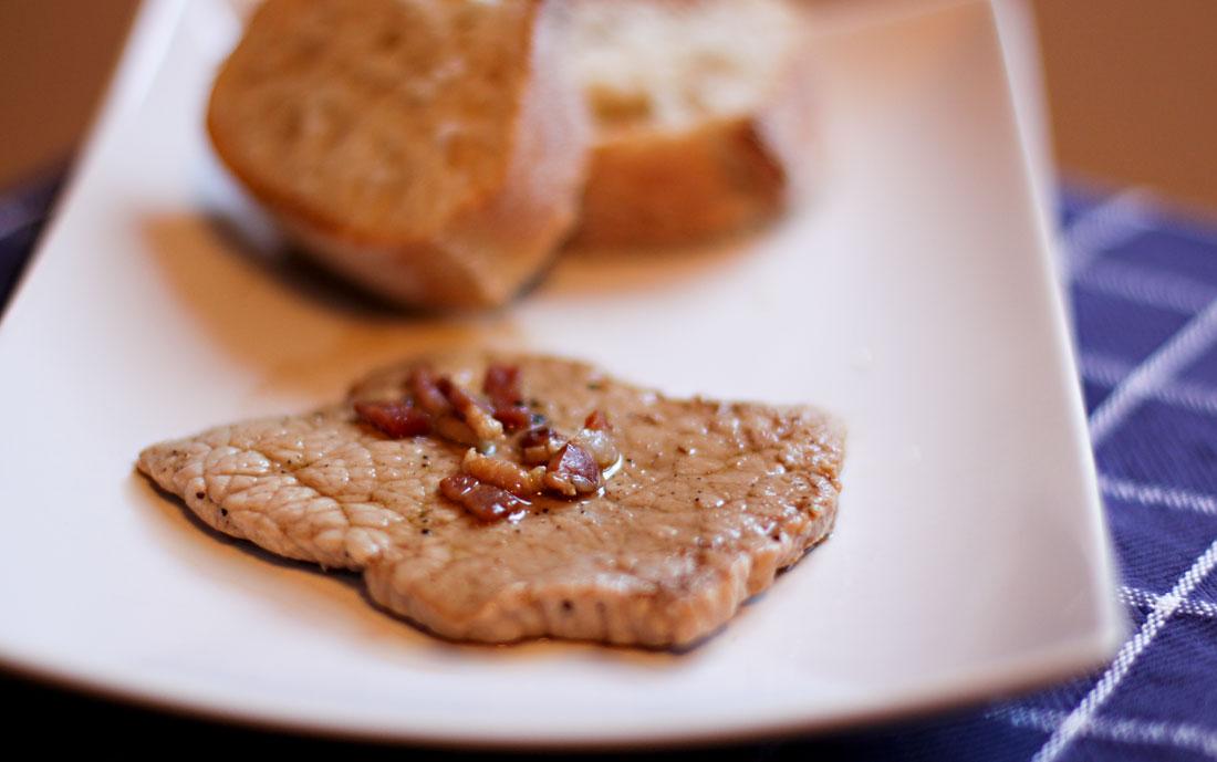 Auf einem Teller liegt ein Kalbsschnitzel mit Speckwürfeln in Marsalasauce. Im Hintergrund zwei Brotscheiben.