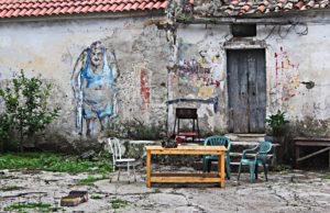 Eine bemalte Hauswand in Agropoli, auf der ein alter Mann in Unterwäsche zu sehen ist. Davoe ein Tisch mit drei Stühlen. Auf dem Tisch sitzt eine Katze.