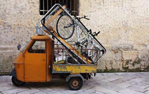 Eine orangene Ape in Lecce, die extrem beladen ist - mit einem Fahrrad, einem Lattenrost und viel Metallschrott.