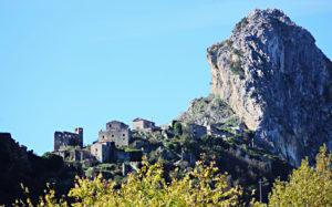 Hoch oben auf dem Berg stehen alte, verlassene Häuser, daneben ein raues Felsmassiv: San Severino di Centola