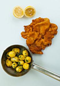 Blick von oben auf einen österreichischen Klassiker: Ein Wiener Schnitzel mit gewellter Panade. Darunter ein Topf mit Petersilien-Kartoffeln. Oberhalb des Schnitzels liegt eine halbierte Zitrone.