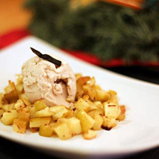 Ein Dessertteller mit Bratapfelkompott mit einer Kugel Haselnusseis in der Mitte