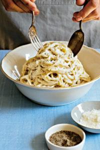 Eine weiße Schüssel mit Spaghetti Cacio e Pepe, die auf einem Tisch mit blauer Tischdecke steht. Jemand richtet sie mit Gabel und Löffel an. Im Vordergrund zwei kleine Schalen mit gemahlenem Pfeffer und Cacio-Käse. (Foto: Kristina Gill)