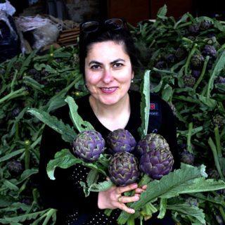 Kochbuchautorin Cettina Vicenzino mit einem Bund großer Artischocken in ihren Händen. Im Hintergrund liegt ein großer Berg aus Artischocken.