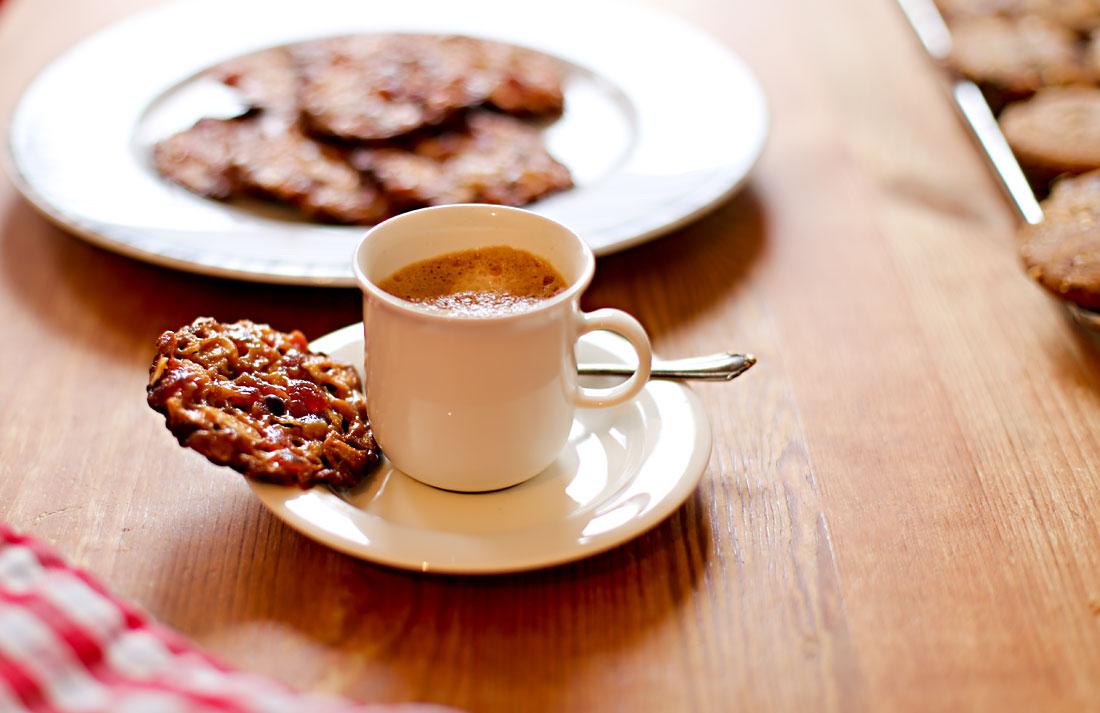 Eine Tasse Espresso mit einem Florentiner Plätzchen, das auf der Untertasse liegt. Im Hintergrund ein Teller mit weiteren Florentinern
