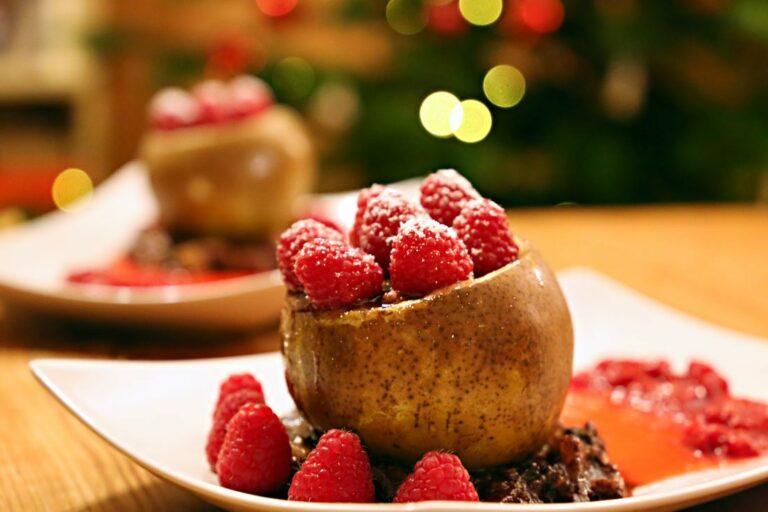 Auf einem Teller steht eine gefüllte Birne in einer Basis aus Schoko-Birnen-Keks-Mischung, verziert mit Himbeeren. Auch die Birne ist an der Schnittfläche mit Himbeeren verziert und mit Puderzucker bestäubt.