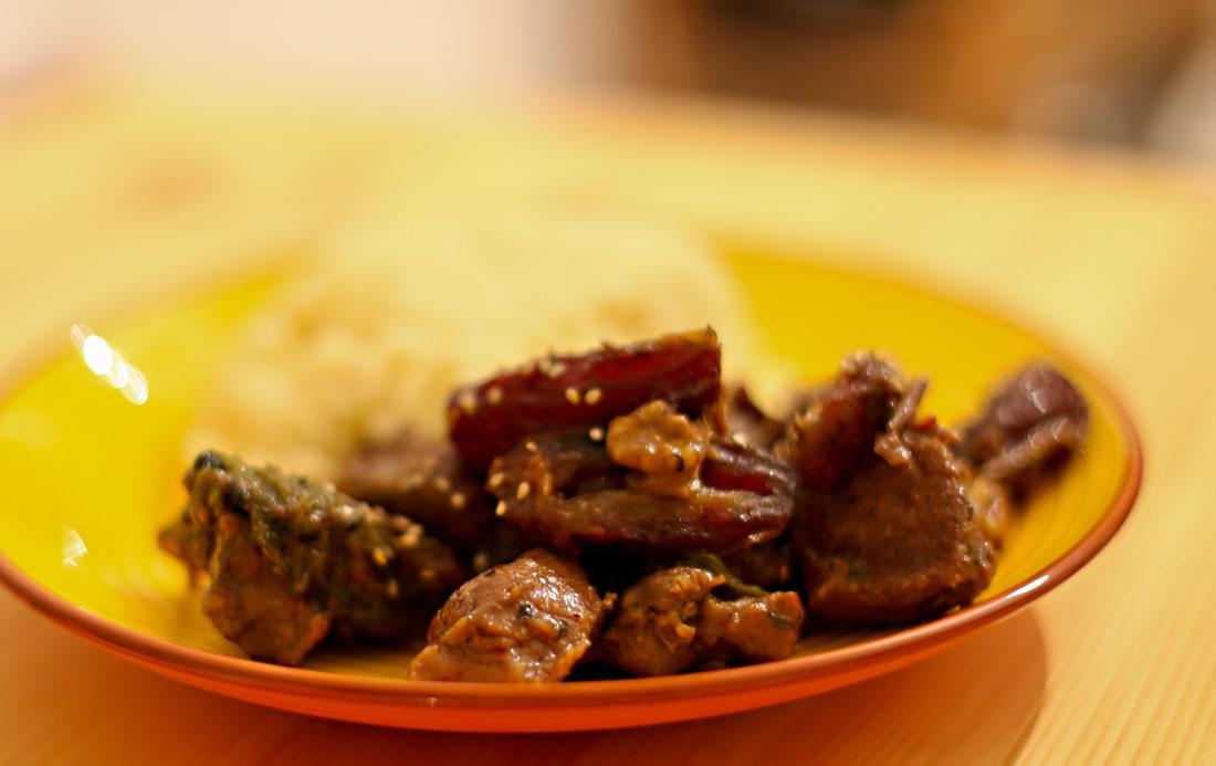 Abbildung eines Tellers, auf dem geschmortes Lammfleisch mit Datteln und Walnüssen sowie Couscous liegt.