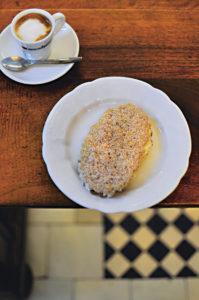 Ein Teller mit einem Teigblatt mit Buttercremefüllung, links davon eine Tasse Espresso Macchiato (Foto: Cettina Vicenzino/ Christian Verlag)