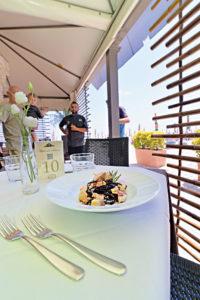 In einem sonnigen Strandrestaurant steht auf einem Tisch ein Teller frische Pasta mit Stockfisch, Pancetta und Schäfskäse