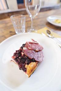 Ein kleines Stück Pan dolce toscano, das mit zwei Scheiben Salami garniert ist.