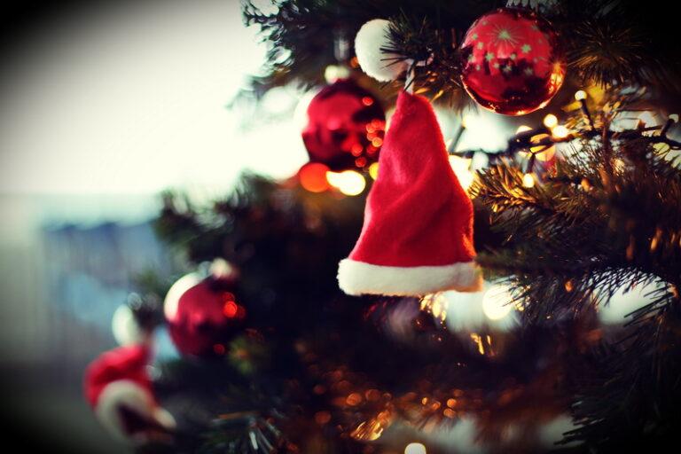 Ein Tannenzweig vom Weihnachtsbaum, an dem im Hintergrund rote Glaskugeln hängen und im Vordergrund eine kleine Weihnachtsmann-Mütze