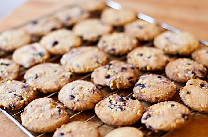 Auf einem Kuchengitter kühlen frisch gebackene Zimtkekse mit Blaubeeren und Cranberries aus.