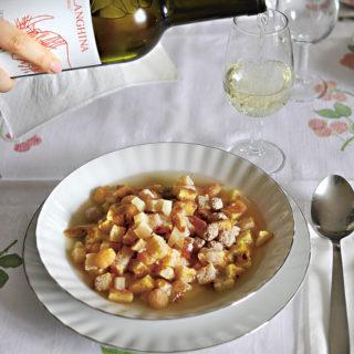 Ein Teller mit Zuppa alla Santé, im Hintergrund wird ein Falanghina in ein Glas eingeschenkt.