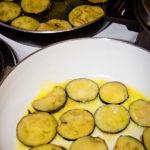 Zwei Pfannen, in denen Auberginenscheiben in Olivenöl frittiert werden.