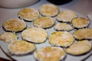 In Mehl gewendete Auberginenscheiben auf einem Teller.