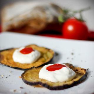 Ein Teller mit zwei frittierten Auberginenscheiben, die jeweils mit einem etwas Knoblauch-Joghurt und einem Klecks Tomatensauce angerichtet sind.