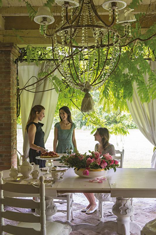 Eine überdachte Terasse mit viel Grün. Auf einem weißen Tisch steht ein Kaffeegedeck, dahinter drei Frauen im Gespräch.