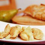 Auf einem rechteckigen Teller ist gebratenes Hühnerfleisch mit Birnen und Marsalasauce angerichtet.