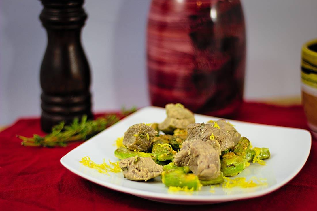 Ein Teller mit Lammfleisch auf grünem Spargel, garniert mit geriebener Zitronenschale
